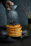 Pancakes with berries on top being sprinkled with confectioners sugar
