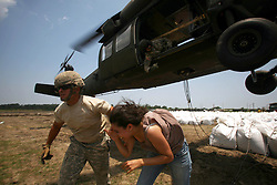 09 June 2010. Fort Jackson, Venice, Louisiana.<br /> France-Soir foreign correspondent Alexandra Gonzalez accompanies Soldiers from the843rd Engineering Company Louisiana National Guard as they load giant sand bags in operation 'Pelican Island Mission' as they struggle to reinforce fragile barrier islands in an effort top stem the flow of BP's catastrophic oil spill as it washes ashore.<br /> Photo; Charlie Varley/varleypix.com