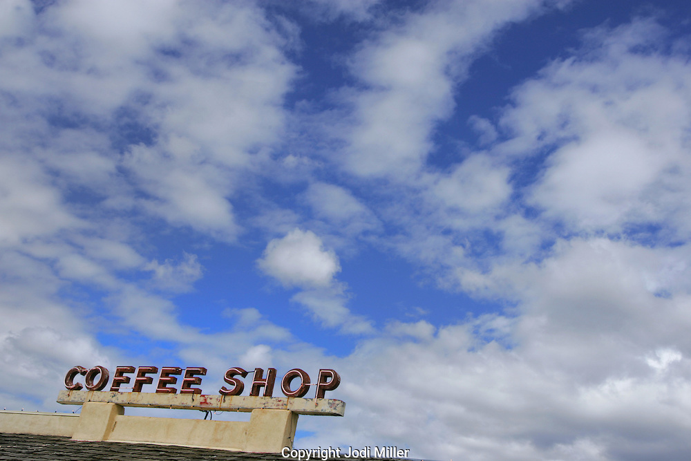 Coffee Shop sign with cloudy sky.