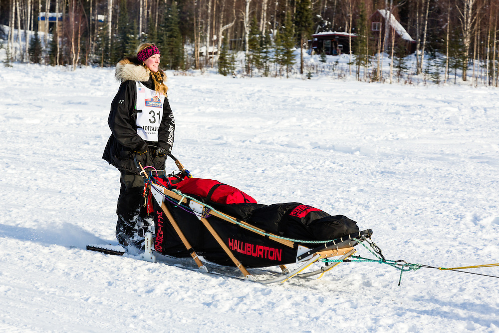 Musher Anna Berington competing in the 41st Iditarod Trail Sled Dog Race on Long Lake after leaving the Willow Lake area at the restart in Southcentral Alaska.  Afternoon.