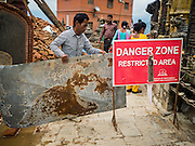 31 JULY 2015 - KATHMANDU, NEPAL: A workers closes a part of Swayambhunath because of dangers from the earthquake. Swayambhunath, also known as the Monkey Temple, is a complex of Buddhist and Hindu temples in Kathmandu. It was heavily damaged in the Nepal Earthquake. The Nepal Earthquake on April 25, 2015, (also known as the Gorkha earthquake) killed more than 9,000 people and injured more than 23,000. It had a magnitude of 7.8. The epicenter was east of the district of Lamjung, and its hypocenter was at a depth of approximately 15km (9.3mi). It was the worst natural disaster to strike Nepal since the 1934 Nepal–Bihar earthquake. The earthquake triggered an avalanche on Mount Everest, killing at least 19. The earthquake also set off an avalanche in the Langtang valley, where 250 people were reported missing. Hundreds of thousands of people were made homeless with entire villages flattened across many districts of the country. Centuries-old buildings were destroyed at UNESCO World Heritage sites in the Kathmandu Valley, including some at the Kathmandu Durbar Square, the Patan Durbar Squar, the Bhaktapur Durbar Square, the Changu Narayan Temple and the Swayambhunath Stupa. Geophysicists and other experts had warned for decades that Nepal was vulnerable to a deadly earthquake, particularly because of its geology, urbanization, and architecture.        PHOTO BY JACK KURTZ