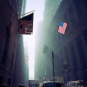 The Monday morning following the attacks on the World Trade Center on Septmber 11th we see a dust-filled haze on Wall Street to where city financiers returned to their office desks to find their city skyline missing the Twin Towers and Manhattan in a state of perpetual shock and still under a mist of smoke from the debris at Ground Zero. To celebrate the near-return to financial normality, New Yorkers' spirit was proved intact by the hanging of US flags from buildings. An American flag hangs and a banner for 48 Wall Street, known as the Bank of New York Building (built in 1928 on land used by the bank since 1797), on the corner of Wall Street and William Street in New York City's Financial District...