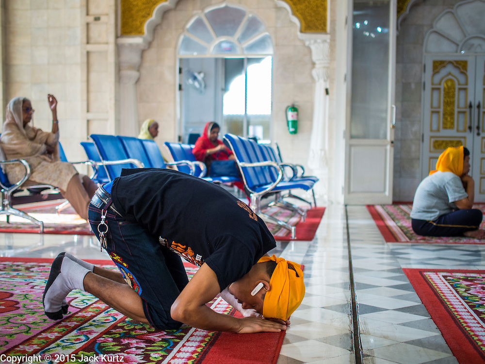 """08 FEBRUARY 2015  BANGKOK, THAILAND:  A man prays in the Darbar Sahib (prayer hall) at Gurdwara Siri Guru Singh Sabha, the Sikh temple in Bangkok. Thailand has a small but influential Sikh community. Sikhs started coming to Thailand, then Siam, in the 1890s. There are now several thousand Thai-Indian Sikh families. Gurdwara Siri Guru Singh Sabha was established in 1913. Construction of the current building, adjacent to the original Gurdwara (""""Gateway to the Guru""""), started in 1979 and was finished in 1981. The Sikh community serves a daily free vegetarian meal at the Gurdwara that is available to people of any faith and background.   PHOTO BY JACK KURTZ"""