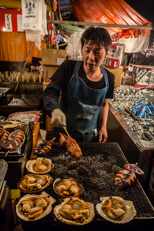 A man seels scallops and ikayaki (grilled squids on a stick), which are common in japanese fairs and festivals