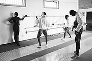 Prison guard Fatoumata Sy monitors minors incarcerated at a nearby prison as they participate in a fencing session at a studio in the city of Thiès, Senegal on April 14, 2015. Supported by OSIWA, organisation 'Pour un sourire d'enfant'  has implemented the sport of fencing as a form of restorative justice in a minor's prison for males and females in the city of Thiès, Senegal. This innovative judicial method works as a restorative rather than punitive approach to justice. Fencing is an effective method for helping incarcerated young people build self-confidence and respect (both for themselves and others), and engender discipline and determination.