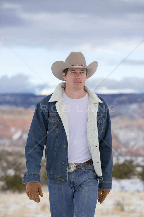 hot cowboy walking on a mountain range