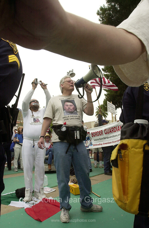"Counter protestor, Roy Warden, shouts to protesters at a demonstration against immigration legislation attended by about 15,000 on April 10, 2006, at Armory Park in Tucson, Arizona.  He chanted, ""Viva Zapata....Return home and fight for your rights.....Respect your own revolution tradition."" They also said, ""You people have been betrayed by communism.""  Protestors of immigration legislation responded with, ""Si se puede,"" and ""We didn't cross the border, the border crossed us."""