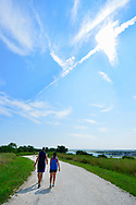 Merrick, New York, USA. August 21, 2017. During Partial Solar Eclipse, two people walk along hilltop trail at Norman J Levy Park and Preserve, the highest point on the South Shore of Long Island. The solar eclipse was 70% at maximum point. The partially eclipsed sun is where tow contrails intersect at upper right of sky.