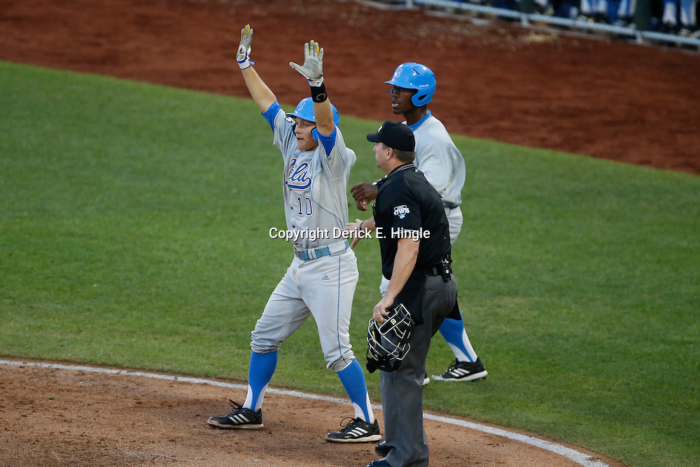 Jun 24, 2013; Omaha, NE, USA; UCLA Bruins shortstop Pat Valaika (10) signals after UCLA Bruins left fielder Brenton Allen (back) scored during the fourth inning in game 1 of the College World Series finals against the Mississippi State Bulldogs at TD Ameritrade Park. Mandatory Credit: Derick E. Hingle-USA TODAY Sports