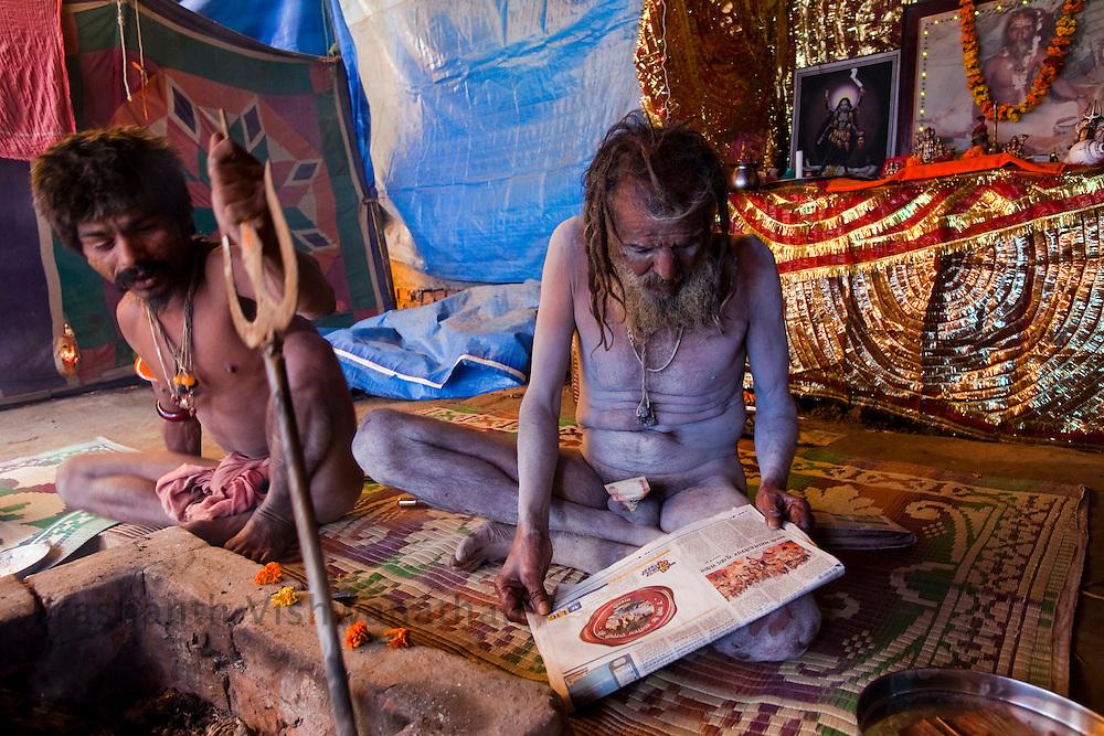 A naked Naga sadhu reads a newspaper at a akhara during he Maha Kumbh ceremony in Haridwar, February 10, 2010.  Photographer:Prashanth Vishwanathan