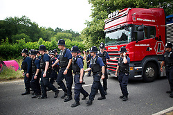 © London News Pictures. 27/07/2013. Balcombe, UK.  Large numbers of police escort a lorry carrying drilling equipment on to the site. Anti Fracking demonstrators and local villagers attempt to blockade a drilling site in Balcombe, West Sussex which has been earmarked for fracking. A number of demonstrators at the site have been arrested. Photo credit: Ben Cawthra/LNP