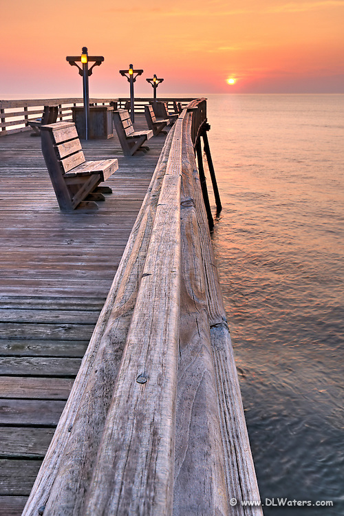 The railing of Kitty Hawk Fishing Pier leads to the sun breaking the horizon.