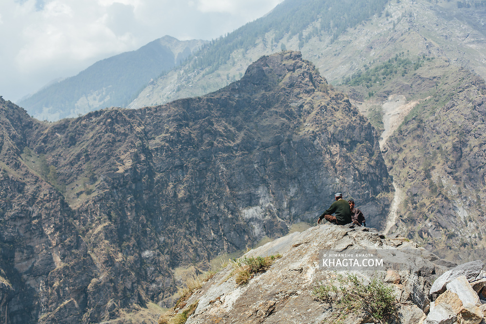 Two men enjoying the view sitting atop a mountain at Nigulsari, a small village on the National Highway 22
