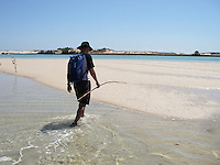 Man walking along sand dunes in the water carrying a spear for crab and fish catching