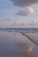 Clouds reflected in the sand at Seminyak Beach in Bali, Indonesia