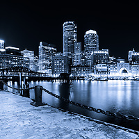 Blue Boston skyline at night photo with the Boston Harborwalk waterfront, downtown Boston skyscrapers and Northern Avenue Bridge.