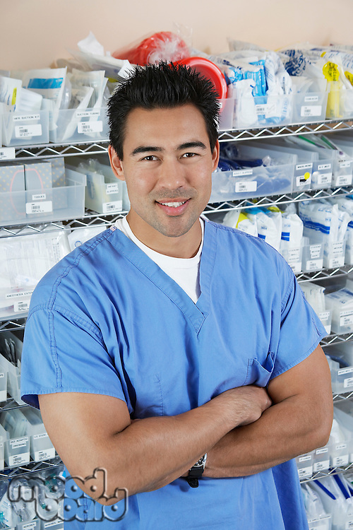 Male nurse standing by shelves with medical supply, portrait