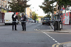 © Licensed to London News Pictures. 27/09/2015. London, UK. Police officers at the cordon on Chatsworth Road next to Regal Pharmacy. Police have launched a murder investigation after a man was shot dead in the street outside Regal Pharmacy next to Mighty Meats butcher shop in Chatsworth Road, Hackney, east London yesterday. Photo credit : Vickie Flores/LNP