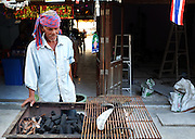 A man prepares a barbecue outside of his restaurant on the island of Ko Tao, Thailand.