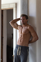 very good looking shirtless man wearing sweatpants at home