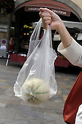 female hand holding up a watermelon in a transparent plastic bag