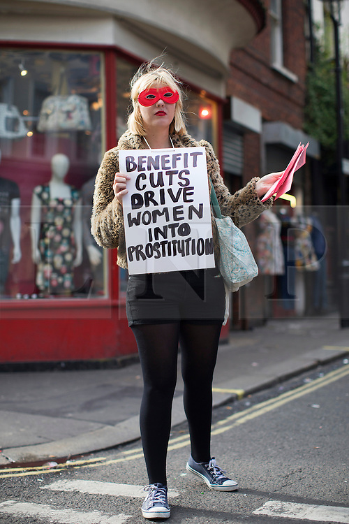 © licensed to London News Pictures. London, UK 09/10/2013. An activist handing out leaflets to protest against evictions of sex workers and the changes being made in Soho by hotel and restaurant developers. Photo credit: Tolga Akmen/LNP