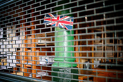 © Licensed to London News Pictures. 14/06/2017. London, UK. A union flag is seen behind a shop's shutters as shop owners and traders get ready for the reopening of Borough Market in London on 14 June 2017, following a terror attack that killed 8 people over a week ago. Photo credit: Tolga Akmen/LNP
