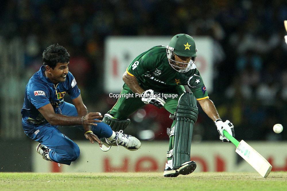 Nuwan Kulasekara beats Mohammad Hafeez to te ball and tries to run him out during the ICC World Twenty20 semi final match between Sri Lanka and Pakistan held at the Premadasa Stadium in Colombo, Sri Lanka on the 4th October 2012<br /> <br /> Photo by Ron Gaunt/SPORTZPICS