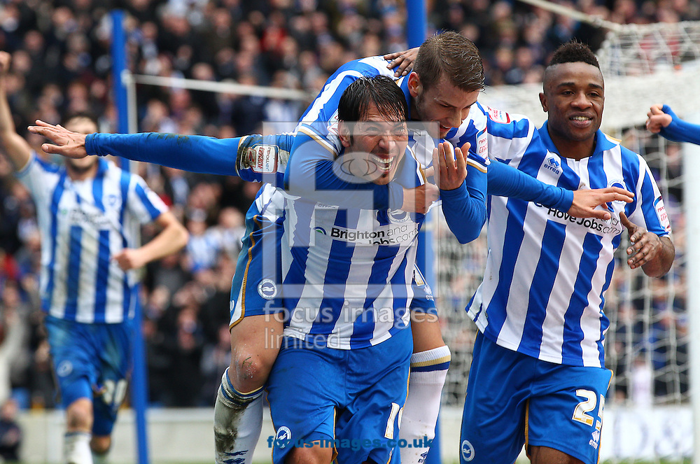 Picture by Paul Terry/Focus Images Ltd +44 7545 642257.17/03/2013.Leonardo Ulloa ( L ) of Brighton and Hove Albion celebrates with Andrea Orlandi ( C ) and Kazenga LuaLua after he scores the opening goal during the npower Championship match at the American Express Community Stadium, Brighton and Hove.