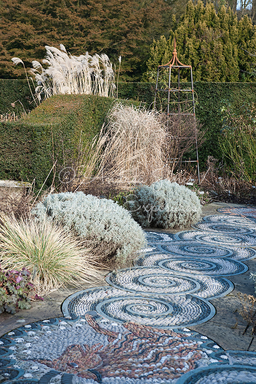 The Pink garden in winter with pebble mosaic paving by Maggie Howarth, ornamental grasses, herbs, clipped yew hedges and metal frame support for climbers at Gresgarth Hall & Gardens, Lancashire, England