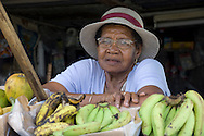 A woman selling bananas at a roadside stall;  St Lucia, The Windward Islands<br /> The Caribbean