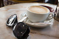 Sunglasses and coffee cup on a cafe table in Nice the South of France