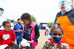 """Young girls collect their food parcels at a """"Safe Zone"""" in Vanwyk'svlei, Wellington, Western Cape, South Africa.(Picture: JULIAN GOLDSWAIN)"""