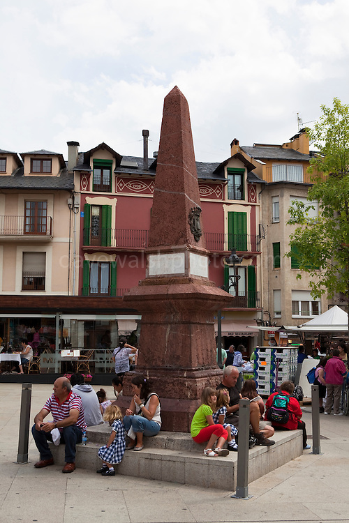 People stting at a monument at Placa de Santa Maria, Puigcerda, Sunday morning, August 2011
