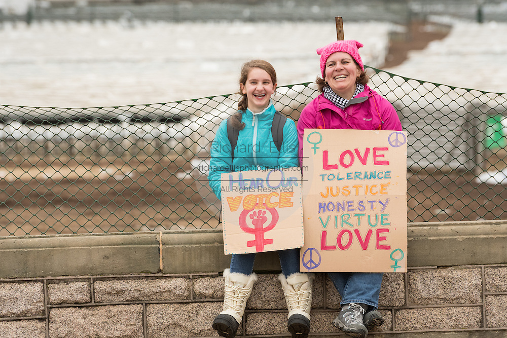 A mother and daughter rest during the Women's March on Washington in protest to President Donald Trump January 21, 2017 in Washington, DC. More than 500,000 people crammed the National Mall in a peaceful and festival rally in a rebuke of the new president.