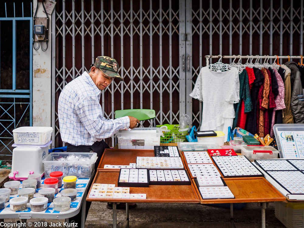 22 DECEMBER 2018 - CHANTABURI, THAILAND: A Thai gem seller sets up his table on the edge of the Chantaburi gem market. The gem market in Chantaburi, a provincial town in eastern Thailand, is open on weekends. Chantaburi used to be an active gem mining area in Thailand, but the mines are played out now. Now buyers and sellers come from around the world to Chantaburi for the weekend market. Many of the stones come from Myanmar, others come from mines in Afghanistan and Africa.    PHOTO BY JACK KURTZ
