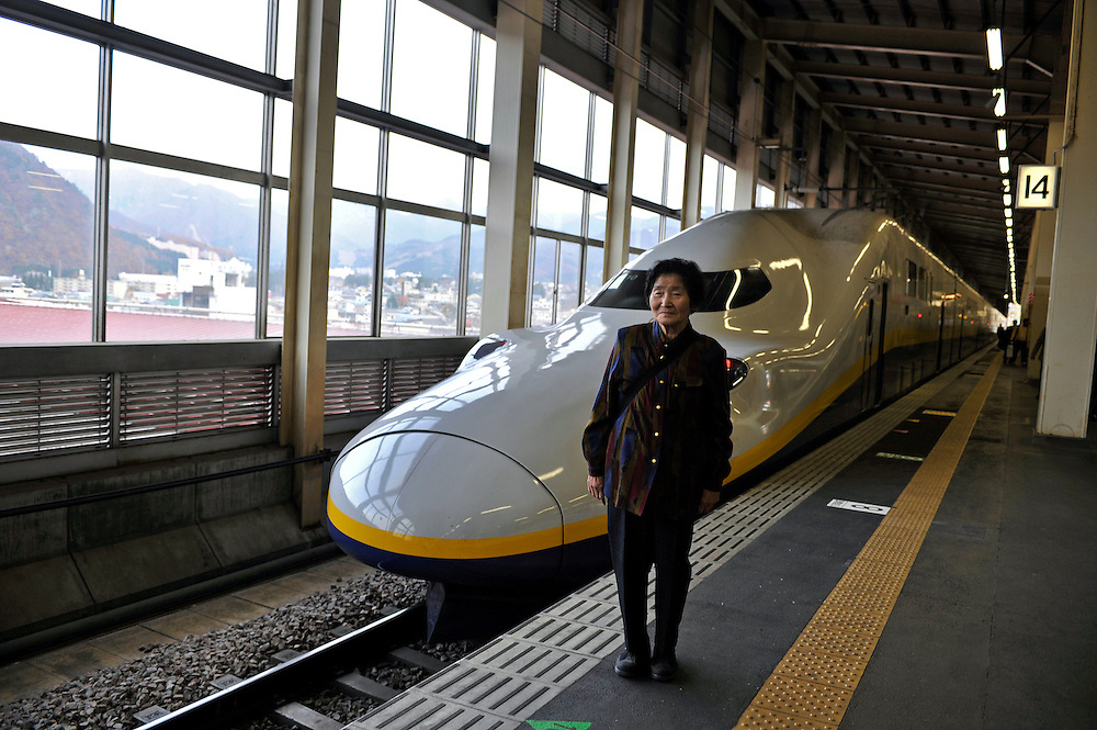 Yuzawa train station.old woman posing in front of a bullet train