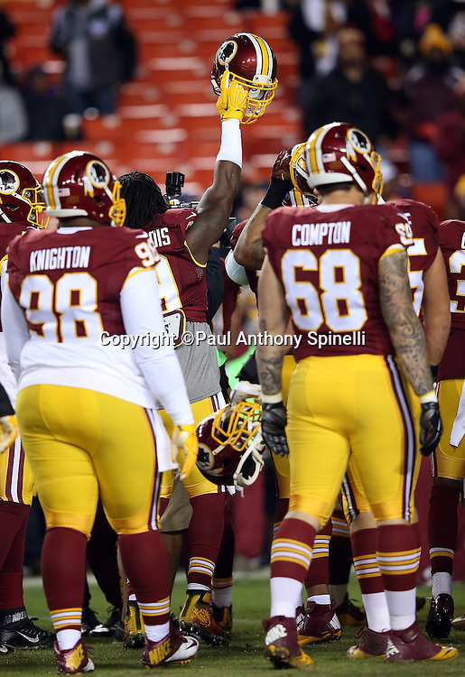 A player holds up his helmet as the Washington Redskins get fired up for the 2015 week 13 regular season NFL football game against the Dallas Cowboys on Monday, Dec. 7, 2015 in Landover, Md. The Cowboys won the game 19-16. (©Paul Anthony Spinelli)