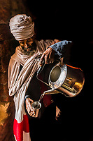 An Ethiopian Orthodox priest pour a cup of holy water in the cave monastery of Neakuto Leab, near Lalibela, northern Ethiopia. The holy water drips from the ceiling of the cave and is collected in a cistern.