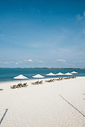 Shaded beach loungers on white sand beach