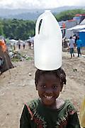 Camp de re?fugie?s Pe?tion-Ville Golf Club, Delmas 48. Aussi appele? le camp Shawn Penn. HRO (Haitian Relief Organization..Hai?ti, dans un camp de de?place?s de Port-au-Prince. Le tremblement de terre de janvier 2010 a force? des centaines de milliers de personnes a? se re?fugier dans des camps de fortune. La distribution d'eau potable est vitale. Cette fillette transportait fie?rement son bidon sur sa te?te.