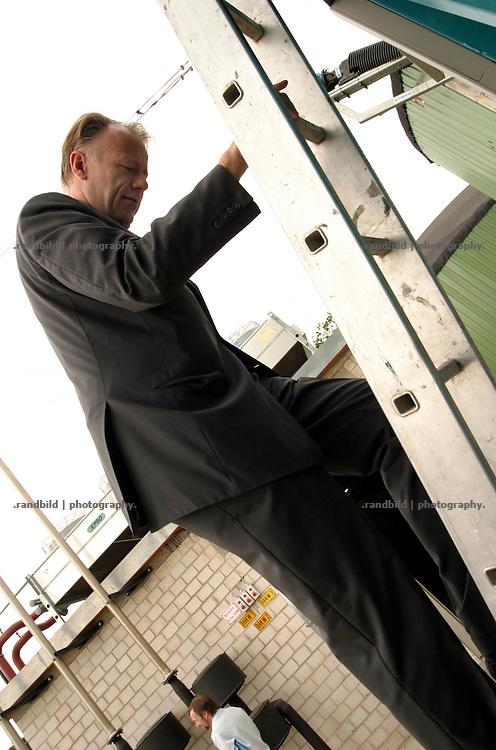 Jürgen Trittin, Bundesumweltminister, steht bei einer Besichtigung einer Biogasanlage im Wendland auf einer Leiter.