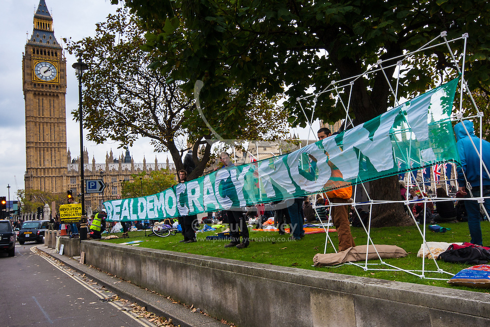 """Parliament Square, London, October 22nd 2014. Protesters from """"Occupy Democracy"""" continue their demonstration against what they say is the hijacking of Britain's democracy by capitalism, where big business is allowed to trample people's rights. Having earlier been removed from Parliament square on grounds that they had damaged the threadbare lawn, they continue to demonstrate outside the closed off space. PICTURED: Activists display a banner calling for """"Real Demoicracy Now""""."""