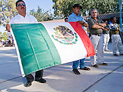02 JULY 2005 - MESA, AZ: Immigrants carry a Mexican flag during a rally for immigrants' rights in Mesa, AZ, July 2, 2005. About 1,000 people attended the rally. Arizona is emerging as a battle ground state in the war over immigration reform. Anti-immigrant groups, like the Minuteman Project, a volunteer border patrol organization, are active in the state and the Republican controlled state legislature is seen as being increasingly anti-immigrant. Immigrants' and Hispanic rights organizations are calling for increased tolerance and greater rights for both legal and illegal immigrants. PHOTO BY JACK KURTZ