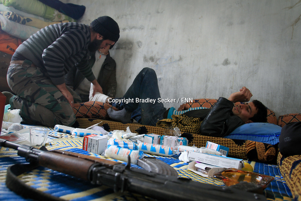 A soldier treats another member of the Free Syrian Army for a broken arm and leg after being injured by Syrian government forces, in a makeshift hospital. Al Janoudiyah, Syria