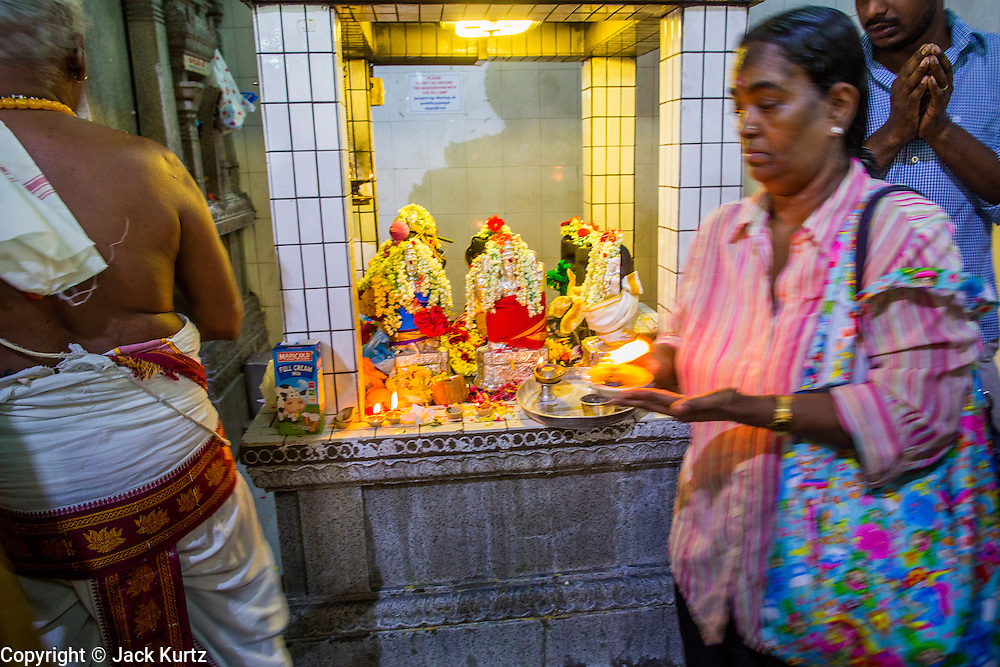22 DECEMBER 2012 - SINGAPORE, SINGAPORE:   People process around Hindu deities during prayers at Sri Veeramakaliamman Temple, a Hindu temple located in Little India in Singapore. The Sri Veeramakaliamman Temple is dedicated to the Hindu goddess Kali, fierce embodiment of Shakti and the god Shiva's wife, Parvati. Kali has always been popular in Bengal, the birthplace of the labourers who built this temple in 1881. Images of Kali within the temple show her wearing a garland of skulls and ripping out the insides of her victims, and Kali sharing more peaceful family moments with her sons Ganesha and Murugan. The building is constructed in the style of South Indian Tamil temples common in Tamil Nadu as opposed to the style of Northeastern Indian Kali temples in Bengal.     PHOTO BY JACK KURTZ