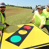 MDOT workers, Jonathan Lepard, Darrell Truelove and Chandler Lacey, remove one of two new redlight signs from their trailer which they installed on the north bound lane of highway 45 just south of the Ripley Road intersection on Thursday morning. MDOT is making improvements to signage at more than 100 intersections across the district, focusing on the more dangerous one.