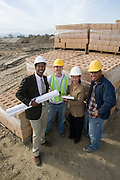 Two architects and two construction workers standing on construction site holding blueprints