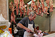 A butcher chops up a lamb in his shop in Capo Market, Palermo, Sicily, Italy. (Supporting image from the project Hungry Planet: What the World Eats)