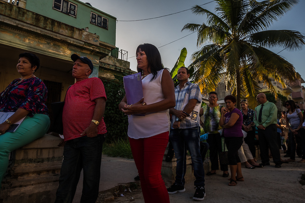 HAVANA, CUBA - JULY 20, 2015: Hundreds of Cuban nationals waited in line outside of the U.S. embassy to apply for visas on Monday morning. After more than half a century defined by mistrust and rancor, the United States officially reopened its six-story embassy in Havana today, marking a watershed moment of transition for the two countries as they lean toward closer diplomatic ties and ease past one of the last remnants of the Cold War.  President Barack Obama, when announcing an end to the diplomatic freeze, eased travel restrictions, opened the door for more remittances to Cuba and expanded the amount of goods that visiting Americans could bring back home – like Cuban cigars and rum. He even removed the country from the list of nations that sponsor terrorism. President Raul Castro, meanwhile, has spent the last five years, before the thaw even began with the Obama administration, attempting to alter his nation's economic dysfunction, ordering the firing of government employees, encouraging a slow but fresh influx of Cubans into self-employment and even creating a special economic zone in the coastal city of Mariel to attract foreign investment.  PHOTO: Meridith Kohut for The New York Times